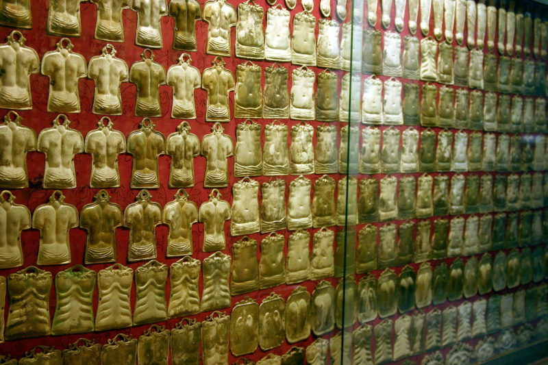 Ex votos hang on a wall in a chapel in Naples. Each one pertains to a part of a body where the person who hung it, or someone they loved, was healed, was healed after much prayer. [photo ref: wikimedia commons]